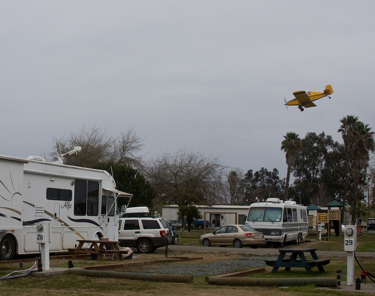 Crop duster Aeroplane lining up above the trees and RVs as it is about to spread insecticide over the adjoining field from the Delta Shores Vista RV Resort near Isleton, California, December 28, 2009. Our Alfa Motorhome is on the left.