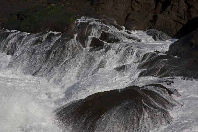 Surf draining off the rocks after a large wave crashed on them along the northern coast of Oregon. Nov 2, 2009