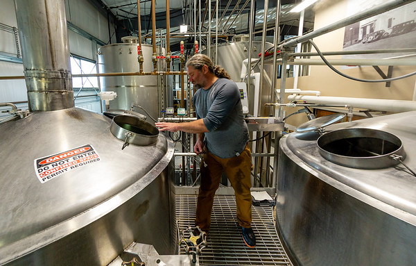 While the mash is cooking (in kettle on right), Dave preps the brew kettle (on left), where the glucose-rich liquid (wort) drawn off the malt-water mix (mash) will boil.