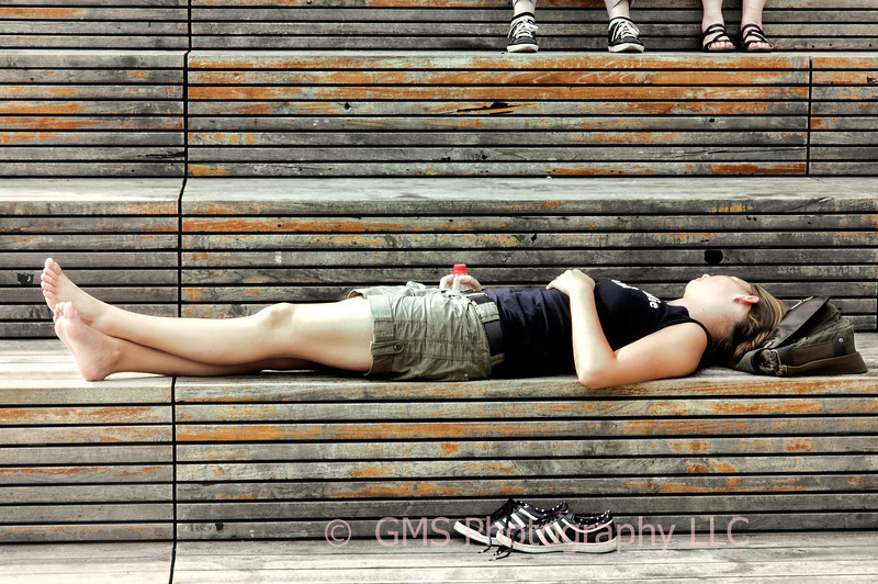 Female takes a break to sleep on a bench on the High Line in NYC.