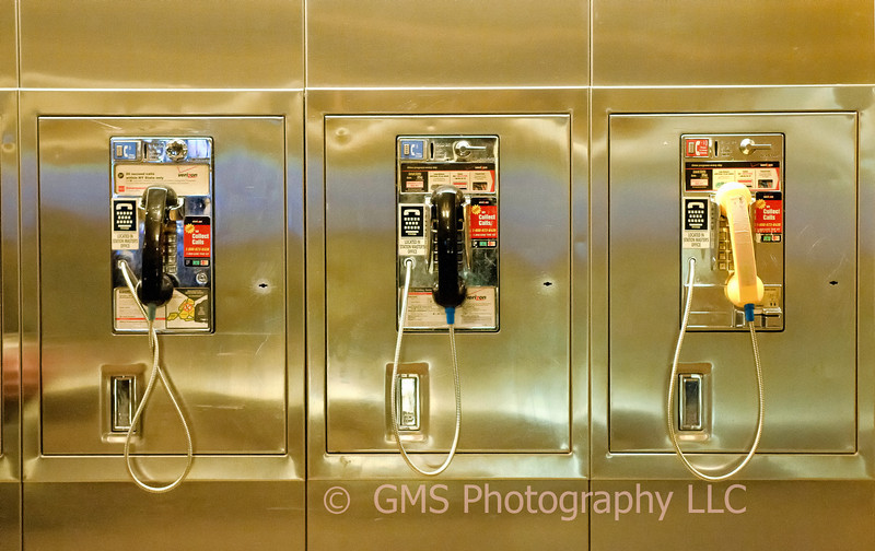 Two Black and one yellow handled pay phones at Grand Central Station in NYC.