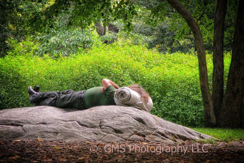 Man sleeps on rock in Central park, New York City