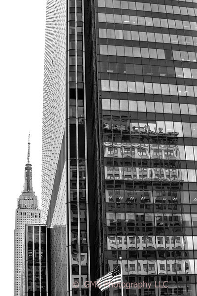 A partial view of Empire State Building in b ackground with companion building in foreground containing reflections in windows and an American flag.