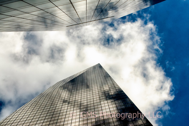 Towers in New York City appear to converge in the clouds.