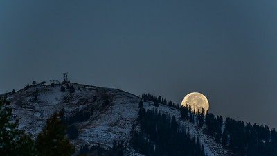 Harvest Full Moon Sets Behind Bald Mountain