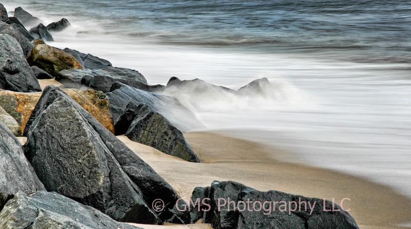 Shoreline Rocks And Opposing Surf