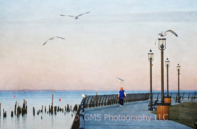A lone individual strolls along the bayside on an early morning in Keyport, New Jersey.