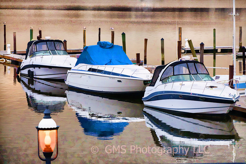 Three boats are docked at the foot of marina adjacent to riverside gardens park in Red Bank, New Jersey with their reflections creating abstract patterns in the Navesink River and park lamp lit in the foreground.