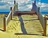An artistic impression of partially sand covered steps with footpronts that transition between indentations on sand above covered steps at bottom to none at the top as the viewer is led to a beautiful sky at the platform.  Sandy Hook New Jersey.
