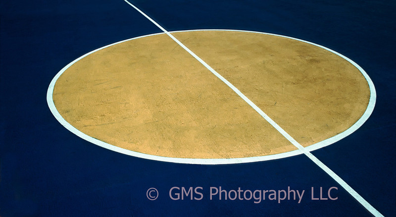 Shapes and colors on outdoor basketball court create interesting intersections of lines and curves.