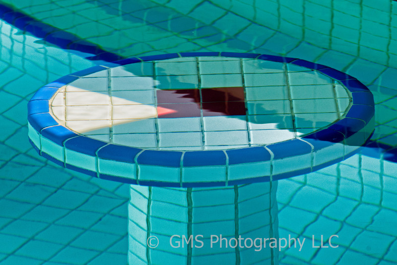 Reflections around tiled seat and wall at bar pool in Whitehouse Jamaica create interesting interseting geometric shapes when sunlitght is included.