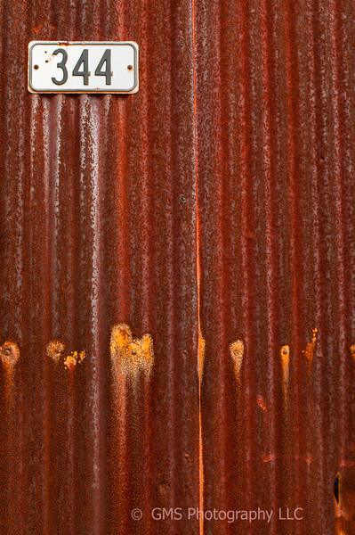 Rust on side of a building is contrasted with the building number that has weathered the elements in relatively good condition.