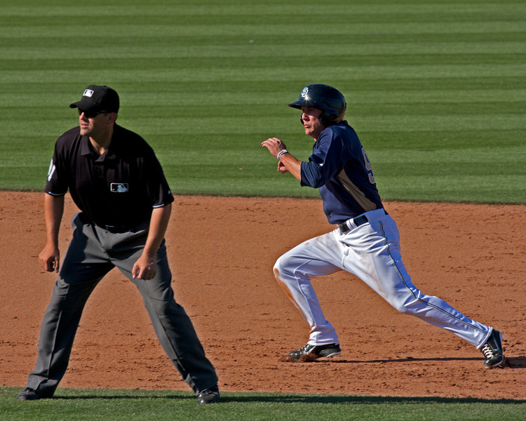 Padres player (with base umpire) running for 3rd base after base hit in Padres vs. Dodgers pre-game training season in Peoria, Arizona. March 26, 2011.