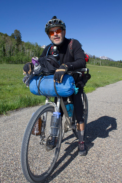 Rich Wolf of Julian, California pauses along Red Rock Road near Island Park, Idaho in the Tour Divide Race from Banff, AB to Antelope Springs, New Mexico. Morning of June 18, 2012.
