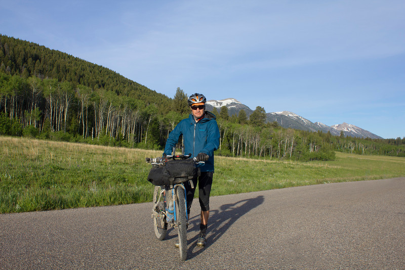Robin Borstmayer of Banff, Alberta, Canada posing along Red Rock Road during the Tour Divide Bicycle race at mile 1008. June 16, 2012.  Robin slept on the grass at RedRock RV park last night. Centennial Mountains are in the background.