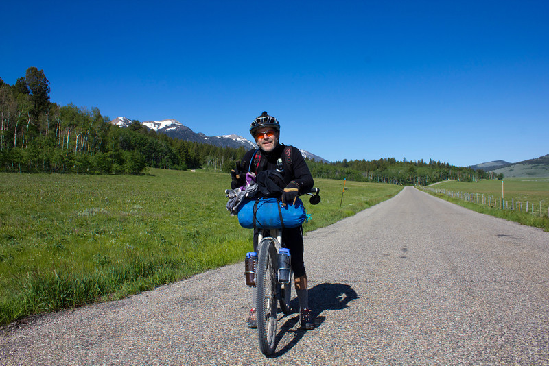 Rich Wolf cycling pauses Red Rock Road near Island Park, Idaho in the Tour Divide Race from Banff, AB to Antelope Springs, New Mexico. Rich is at mile 1009 with only 1700 more miles to finish. His goal is to finish first among the aged 50+ riders. Morning of June 18, 2012.
