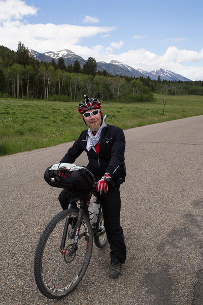 Markley Anderson from Virginia is riding along Red Rock Road near Island Park, Idaho as part of the Tour Divide Bicycle Race from Banff, Alberta, Canada to Antelope Springs, New Mexico (Mexico/USA border). He has stopped for a photo in front of the Centennial Mountains in Idaho at RedRock RV Park.  At this point he is number 7 in a field of 142. Good going Markley! June 20, 2013.
