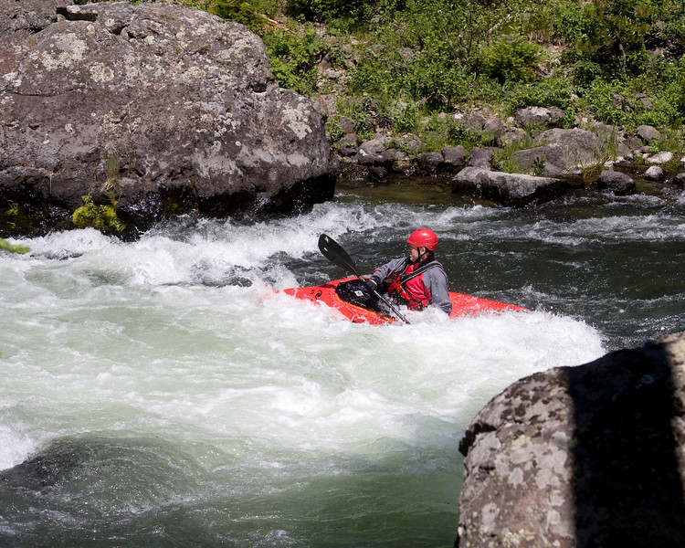 Kayakers on Coffee Pot Rapids (3 rating) along Henry's Fork of the Snake River in Island Park, Idaho. June 28, 2009. This kayaker was part of a large group running these rapids in kayaks.