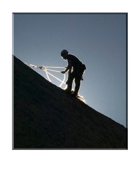 The sun backlights this rock climber at Joshua Tree National Park in California. Feb 07, 2008.