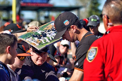 Buster Posey signs autographs before the game