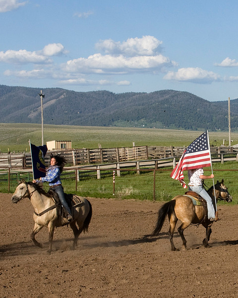 Rodeo girls parading the Idaho and USA flag to start the first rodeo of the season for Meadow Vue Ranch, near RedRock RV Park in Island Park, Idaho. June 24, 2009