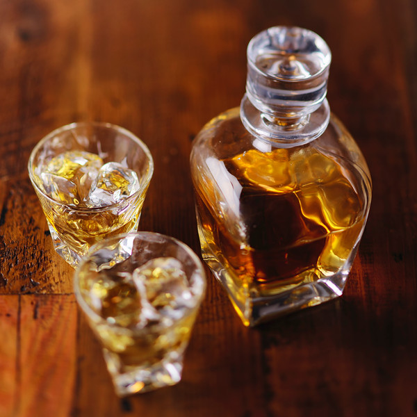 A Whiskey Bottle and Two Glasses of Scotch on the Rocks on a Wooden Table