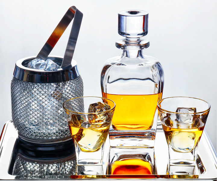 Whiskey in Traditional Decanter and Glasses with Ice Cubes and Ice Bucket on a Silver Tray