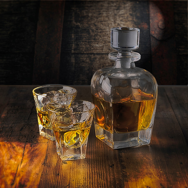 A Whiskey Bottle and Two Glasses on the Rocks on a Wooden Table