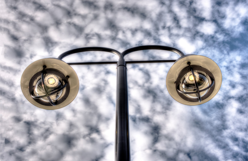 Two Streetlamps Under A Cloudy Sky
