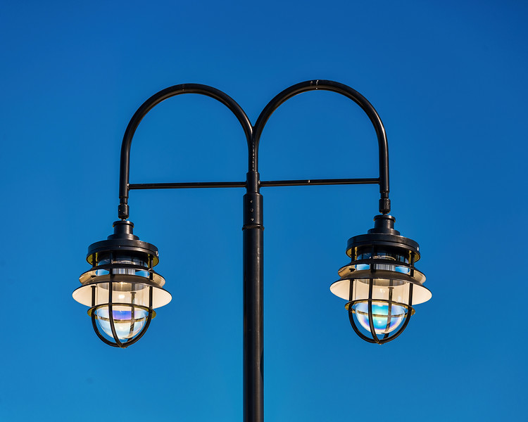 Two Streetlamps Against A Blue Sky