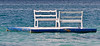 Two empty benches sit on floating platform off the beach in Whitehouse Jamaica