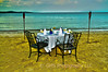 A table is set for sunset dinner on the beach in Whitehouse Jamaica