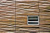 A mundane window on the Highline in New York City is surrounded by patterened metallic siding that is digitally enhanced.