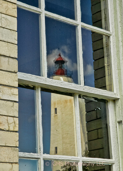 Sandy Hook lighthouse is reflected in window of old firehouse.