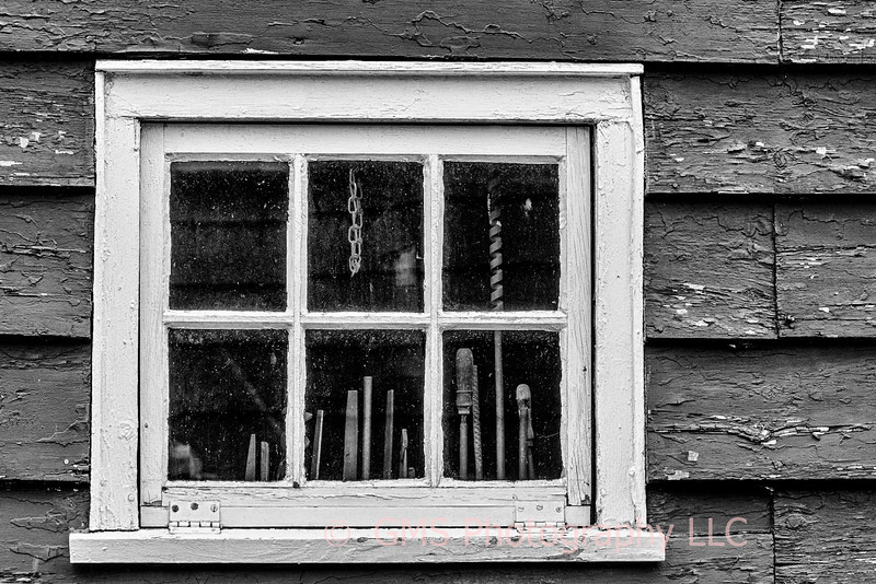 Antique carpenter's toos are visible through workshop window in Historic Holmdel Park in Holmdel, New Jersey.