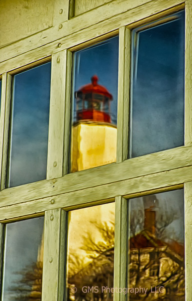 Sandy Hook lighthouse complex is reflected in window of old firehouse.