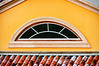 Arch shaped window sits atop colorful tile roof on building in Whitehouse Jamaica