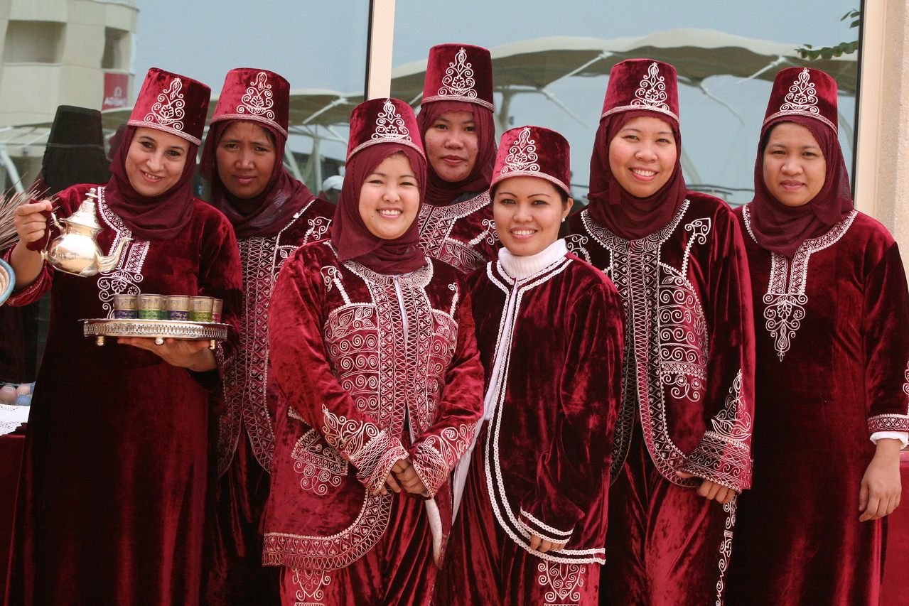 10. Girls dressed in native dress pour Arabic tea for visitors