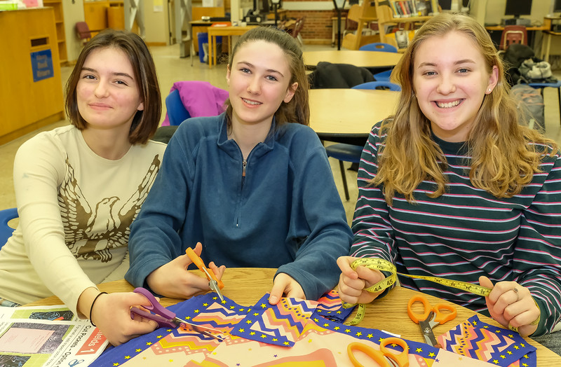 Three lovely Interact volunteers cutting large sheets of colourful fabrics into long strips for final assembly