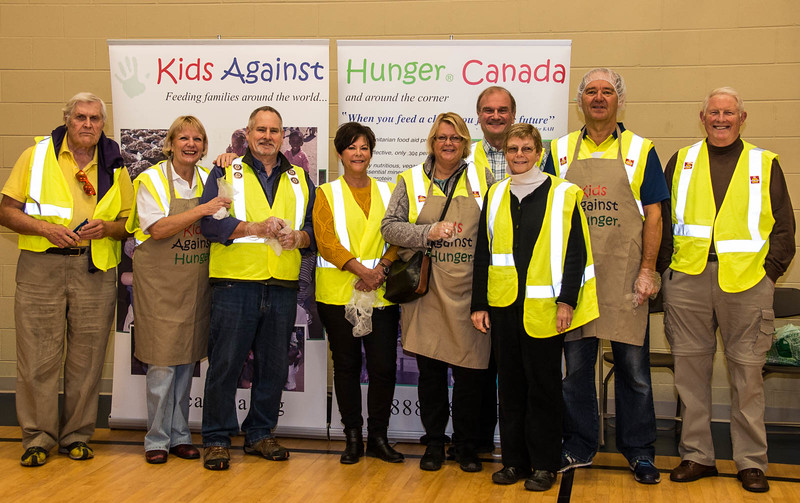 The Rotary Club of Toronto West team in their signature yellow work vests, all ready to start assembling food packs.