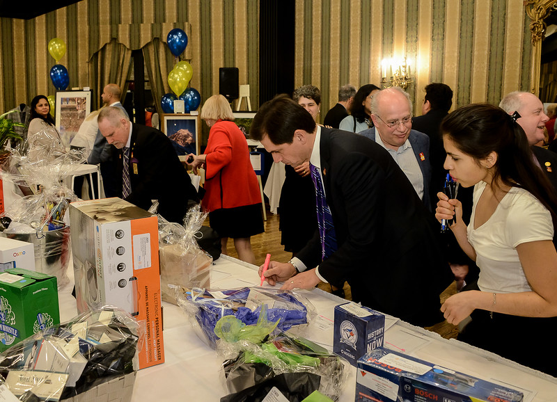 Rotarians and volunteers scrambling to close down a silent auction table after the countdown finishes