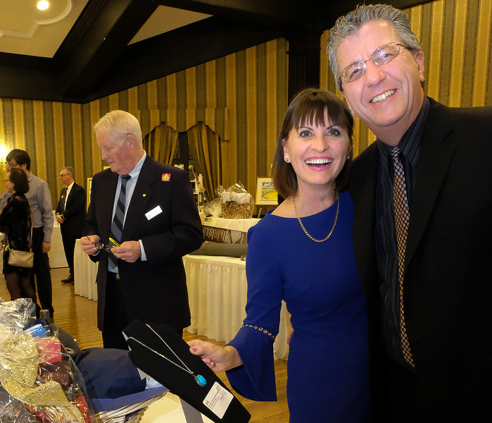Mary Barida,  a supporter of Meagan's Walk,  with guest. Rotarian Bob Sexton perusing the gifts.