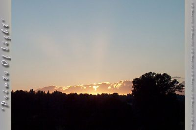 A wider view of the sunset with Rays of Light reaching out into the sky.