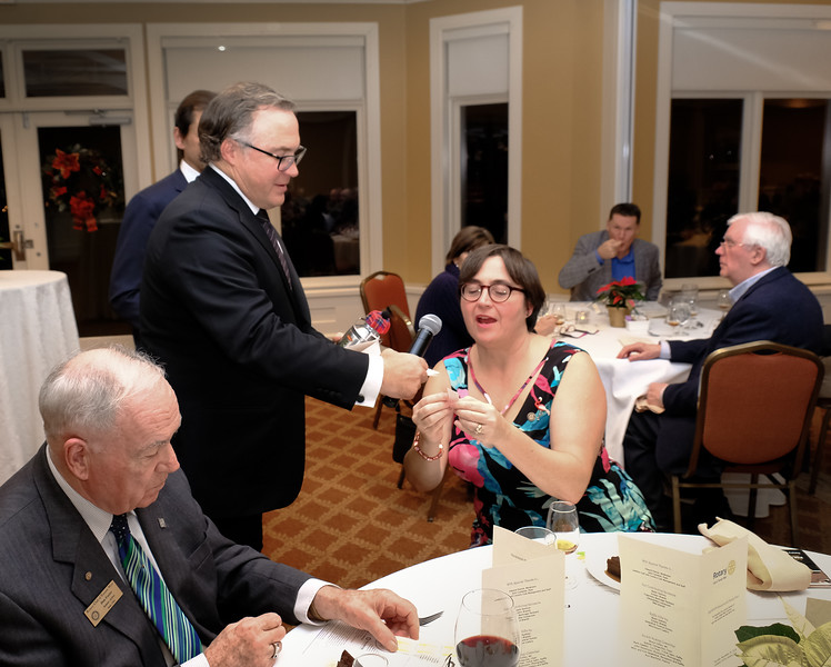 Bruce asks Mary Lou Harrison, Rotary 7070 District Governor to pick a raffle ticket winner. Her proud father Don Foster, seated at far left, is a long time RTW club member.