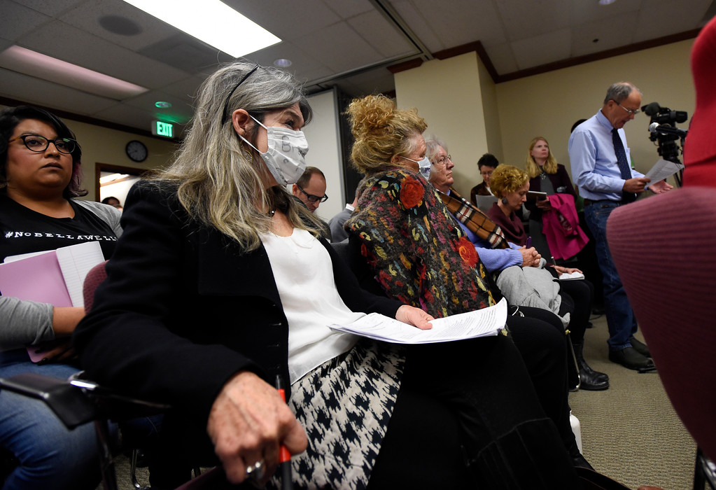 . Gina Hardin, with 350 Colorado, wears a mask as she listens to other concerned residents speak during a public meeting on Monday with the Colorado Oil & Gas Conservation Commission  on Monday at the COGCC corporate office in Denver. The meeting gave citizens a chance to voice opinions on proposed spacing applications by Extraction Oil & Gas in Broomfield. For more photos and video of the meeting go to dailycamera.com Jeremy Papasso/ Staff Photographer/ Oct. 30, 2017