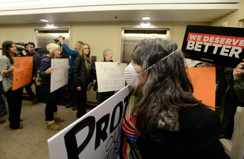 . Lauren Swain, of Denver, wears a mask while chanting with other protesters in the hallway during a public meeting on Monday with the Colorado Oil & Gas Conservation Commission  on Monday at the COGCC corporate office in Denver. The meeting gave citizens a chance to voice opinions on proposed spacing applications by Extraction Oil & Gas in Broomfield. For more photos and video of the meeting go to dailycamera.com Jeremy Papasso/ Staff Photographer/ Oct. 30, 2017