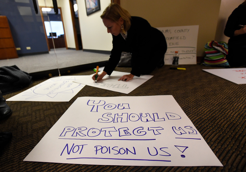 . Kim McNaughton, of Broomfield, makes a sign before protesting during a public meeting on Monday with the Colorado Oil & Gas Conservation Commission  on Monday at the COGCC corporate office in Denver. The meeting gave citizens a chance to voice opinions on proposed spacing applications by Extraction Oil & Gas in Broomfield. For more photos and video of the meeting go to dailycamera.com Jeremy Papasso/ Staff Photographer/ Oct. 30, 2017
