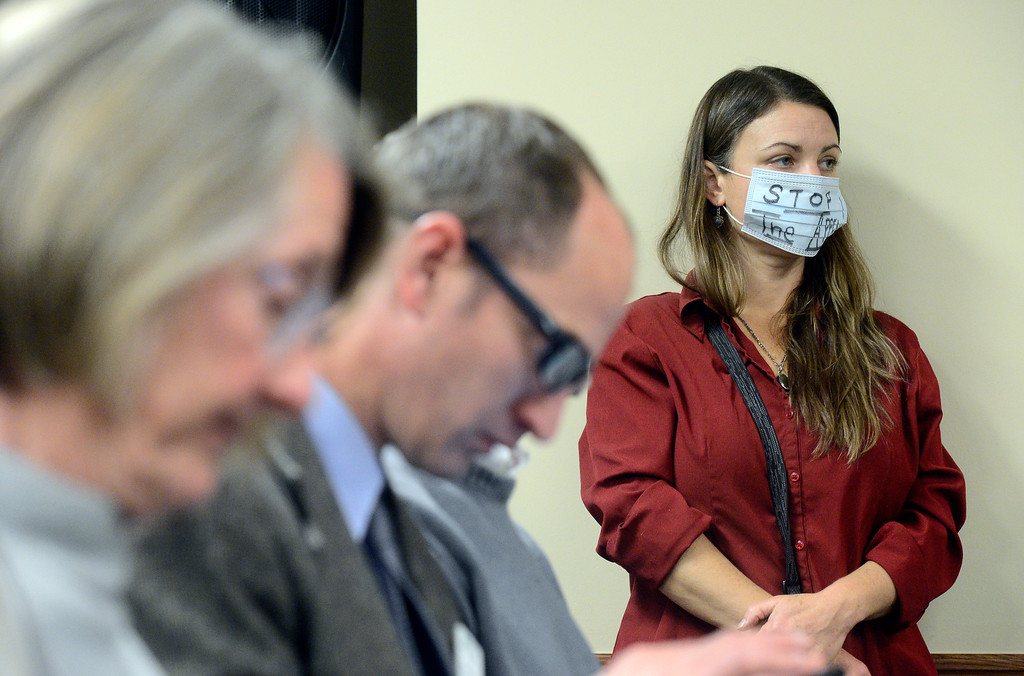 . Micah Parkin, of Boulder, wears a mask as she listens to other concerned citizens speak during a public meeting on Monday with the Colorado Oil & Gas Conservation Commission  on Monday at the COGCC corporate office in Denver. The meeting gave citizens a chance to voice opinions on proposed spacing applications by Extraction Oil & Gas in Broomfield. For more photos and video of the meeting go to dailycamera.com Jeremy Papasso/ Staff Photographer/ Oct. 30, 2017