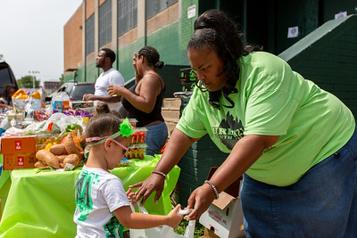Yani Williams hands groceries to Myla Colon, 3, at McVeigh Recreation Center in Kensington, Monday, August 5, 2019. The groceries were donated through Philly Food Rescue and delivered by Williams, of Urban 215 Youth Outreach.