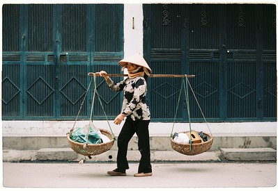 In Hanoi, Vietnam, a woman carries goods through bạch đằng market using baskets that balance on her shoulder.